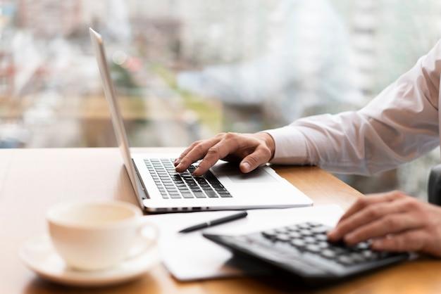 Uomo d'affari che lavora al computer portatile e che fa i calcoli Foto Gratuite