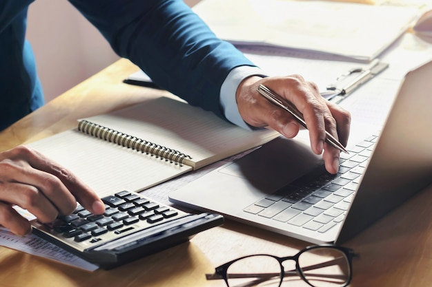 Uomo d'affari che lavora allo scrittorio con l'utilizzo del calcolatore e del computer in ufficio. finanza di contabilità di concetto Foto Premium