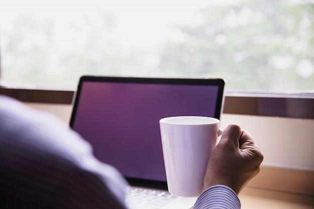 Uomo d'affari che lavora con il computer con la tazza di caffè nella camera d'albergo Foto Gratuite