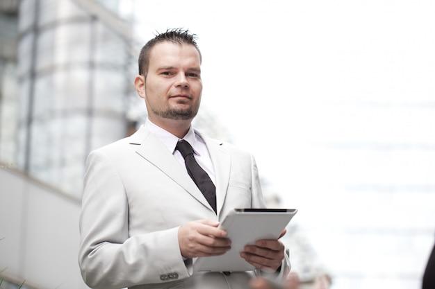 Uomo d'affari che lavora con la compressa digitale nell'ambiente urbano Foto Premium