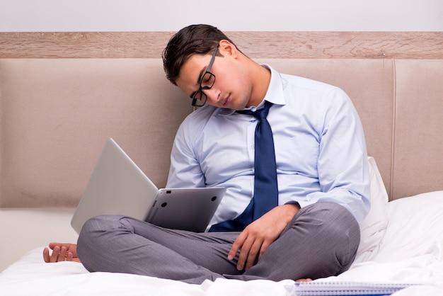 Uomo d'affari che lavora nel letto a casa Foto Premium