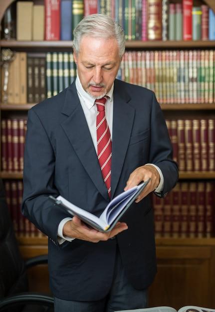 Uomo d'affari che legge un libro in una biblioteca Foto Premium