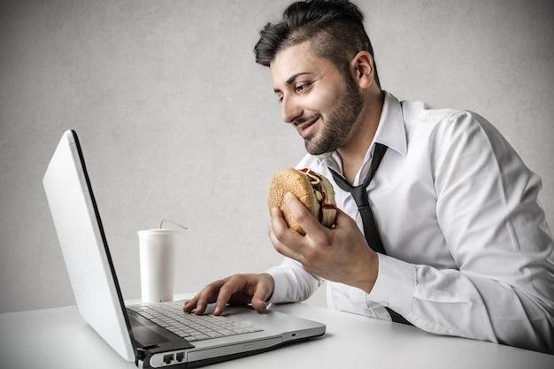 Uomo d'affari che mangia hamburger Foto Premium