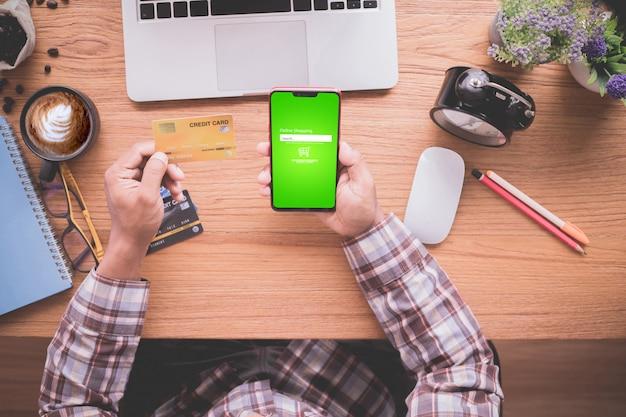 Uomo d'affari che mostra derisione sulla carta di credito e sul telefono cellulare, concetto di acquisto online. Foto Premium