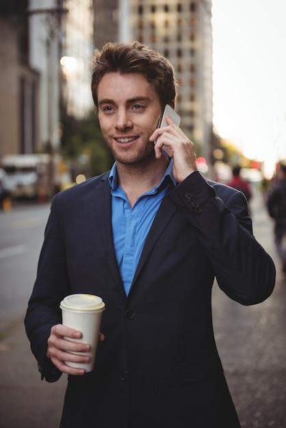 Uomo d'affari che parla sul telefono cellulare e che tiene caffè Foto Gratuite