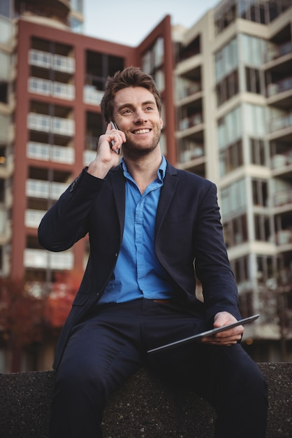 Uomo d'affari che parla sul telefono cellulare e che tiene compressa digitale Foto Gratuite
