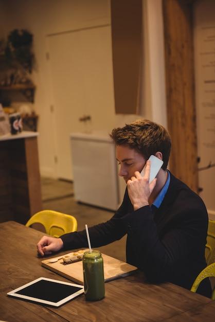 Uomo d'affari che parla sul telefono cellulare Foto Gratuite
