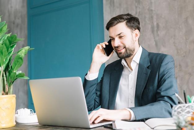 Uomo d'affari che parla sul telefono vicino al computer portatile Foto Gratuite