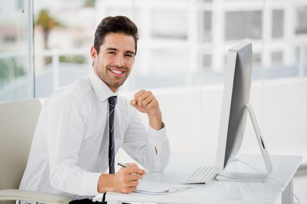 Uomo d'affari che per mezzo del computer e prendendo le note Foto Premium