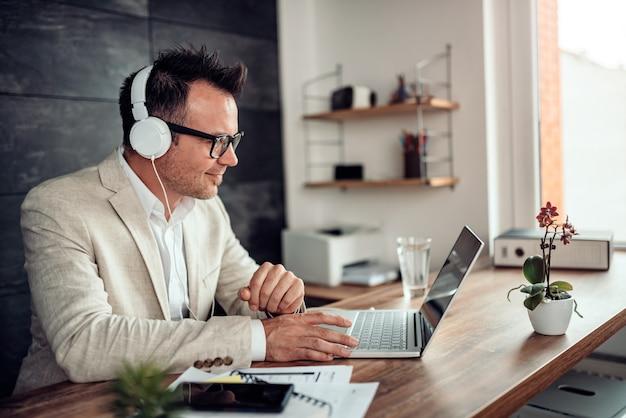 Uomo d'affari che per mezzo del computer portatile e ascoltando musica sulle cuffie Foto Premium