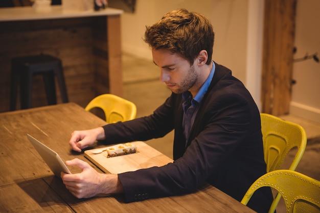 Uomo d'affari che per mezzo della compressa digitale mentre mangiando gli spuntini Foto Gratuite