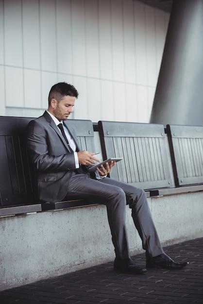 Uomo d'affari che per mezzo della compressa digitale mentre sedendosi su un banco Foto Gratuite
