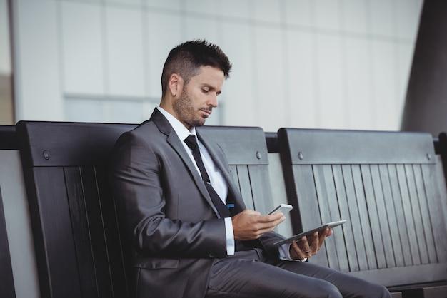 Uomo d'affari che per mezzo della compressa e del telefono cellulare digitali Foto Gratuite