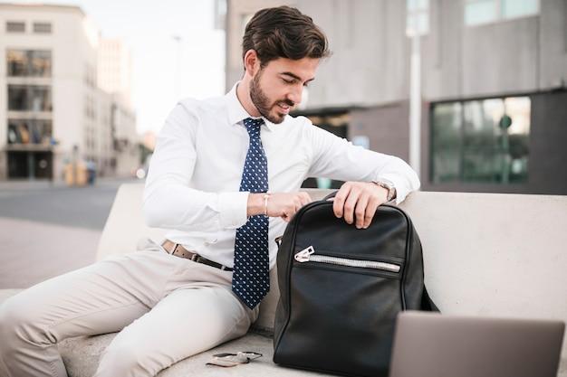 Uomo d'affari che si siede sulla panchina guardando dentro il suo zaino Foto Gratuite