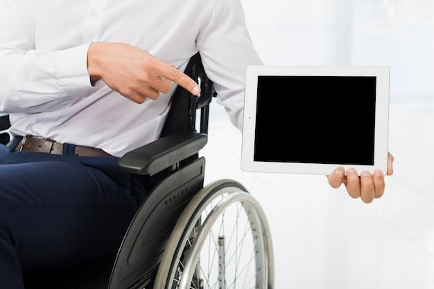 Uomo d'affari che si siede sulla sedia a rotelle che indica il suo dito alla compressa digitale Foto Gratuite