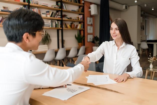Uomo d'affari che stringe le mani su un affare con la giovane donna di affari nella sala per conferenze dell'ufficio Foto Premium