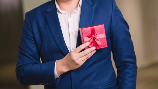 Uomo d'affari che tiene il contenitore di regalo rosso Foto Premium