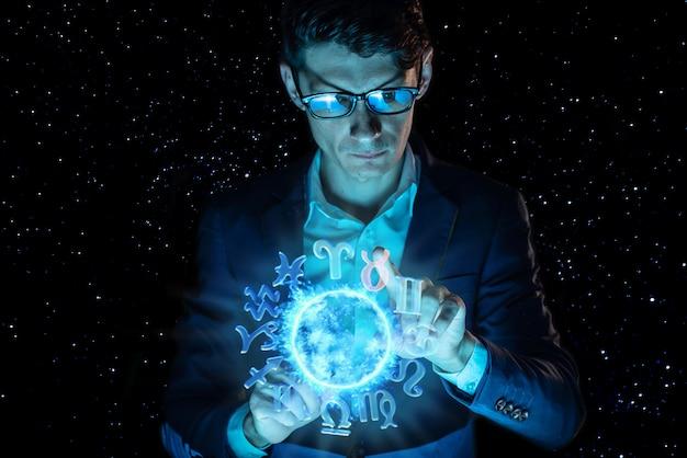 Uomo d'affari che tiene le mani sopra la sfera magica con un oroscopo per predire il futuro. l'astrologia come un business Foto Premium
