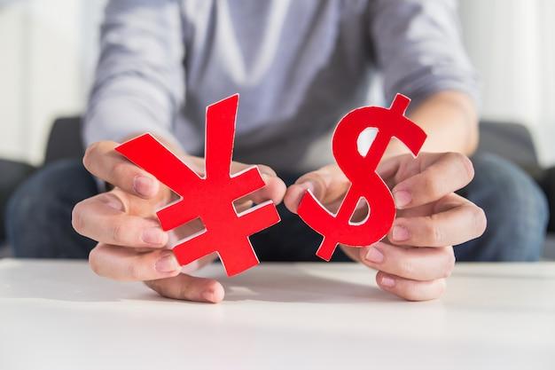 Uomo d'affari che tiene segno del dollaro e cny segno Foto Gratuite