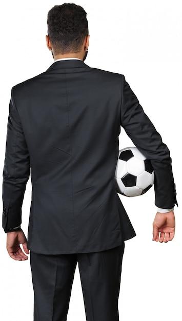Uomo d'affari che tiene un pallone da calcio Foto Premium
