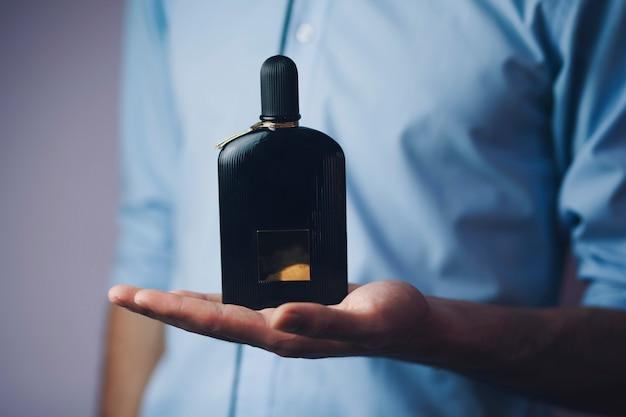 Uomo d'affari che tiene un profumo Foto Premium