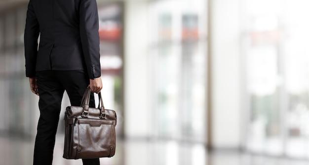 Uomo d'affari che tiene una cartella in un ufficio moderno Foto Premium