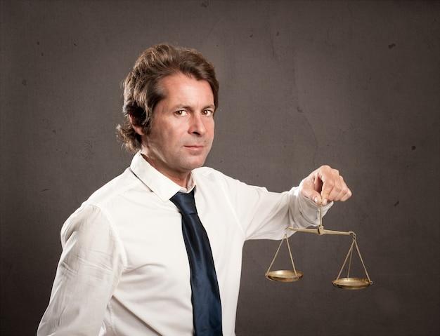 Uomo d'affari che tiene una scala della giustizia Foto Premium