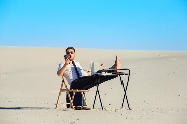 Uomo d'affari che utilizza computer portatile in un deserto Foto Gratuite
