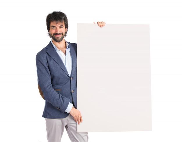 Uomo d'affari con cartello vuoto sopra idolato sfondo bianco Foto Gratuite
