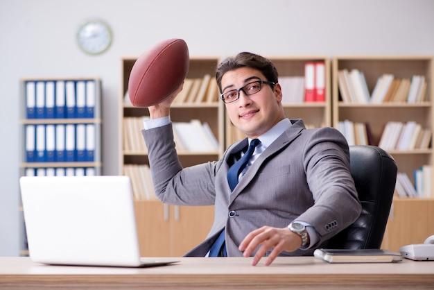 Uomo d'affari con football americano in ufficio Foto Premium