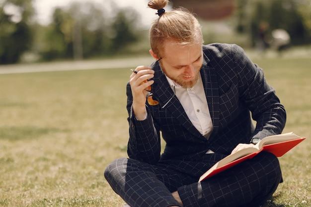 Uomo d'affari con il libro seduto in una città estiva Foto Gratuite