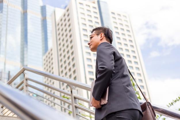 Uomo d'affari con il suo portatile salendo le scale in un'ora di punta a lavorare. affrettati. Foto Premium