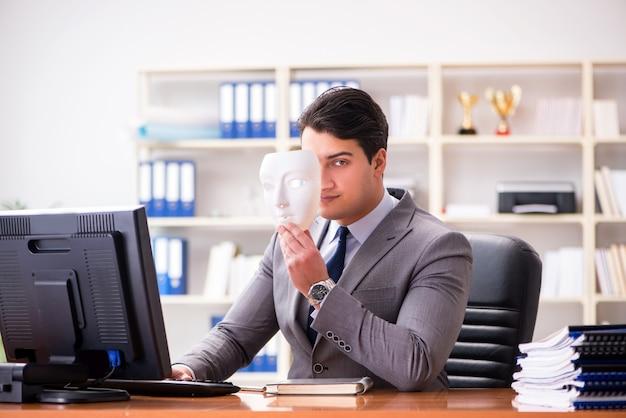 Uomo d'affari con la maschera nel concetto di ipocrisia dell'ufficio Foto Premium