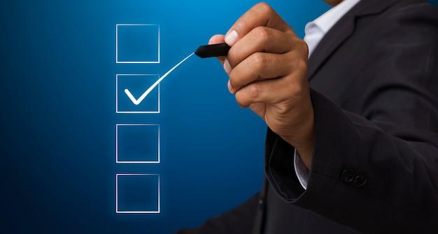 Uomo d'affari con la penna contrassegnare la casella di controllo Foto Premium