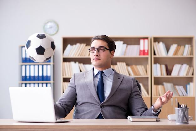 Uomo d'affari con la sfera di calcio in ufficio Foto Premium