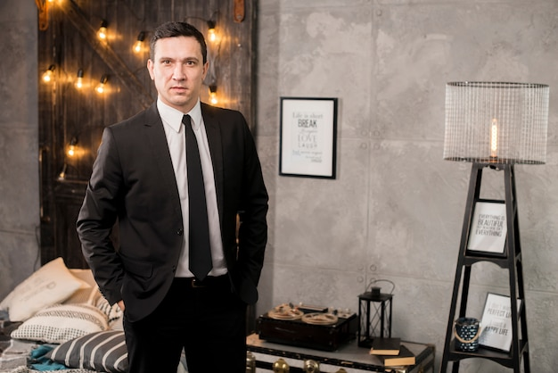 Uomo d'affari con le mani in tasche in piedi nella camera da letto Foto Gratuite
