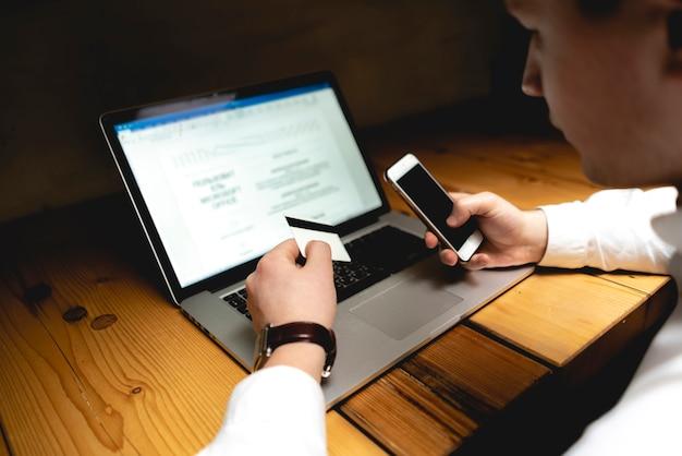 Uomo d'affari con telefono, computer portatile e carta facendo pagamento elettronico sul suo posto di lavoro Foto Premium