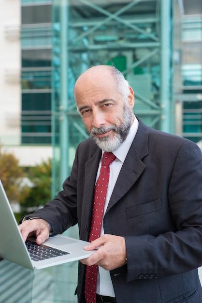 Uomo d'affari dai capelli grigio sicuro positivo che per mezzo del computer portatile Foto Gratuite