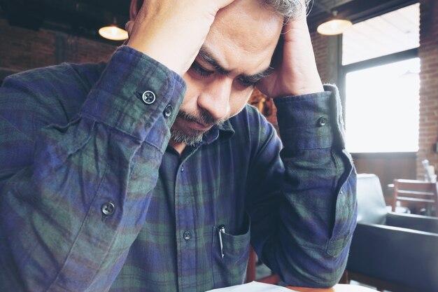 Uomo d'affari di mal di testa che lavora in ufficio Foto Premium