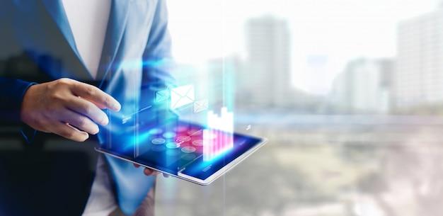 Uomo d'affari di riflessione che per mezzo della compressa che analizza i dati e lo spazio del grafico e della copia del grafico di crescita economica. concetto su tablet con ologramma. Foto Premium
