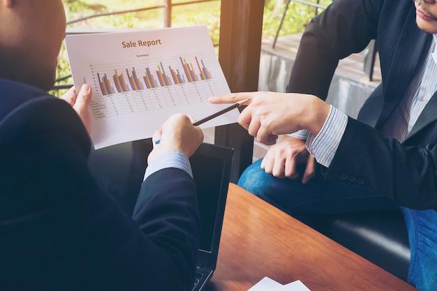 Uomo d'affari due che discute il loro diagramma in caffetteria Foto Gratuite