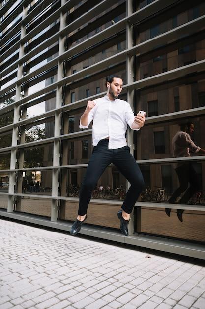 Uomo d'affari emozionante che salta in aria con gioia guardando cellulare Foto Gratuite