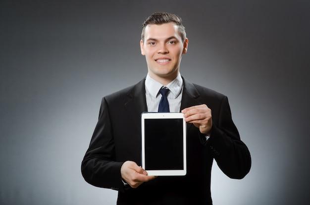 Uomo d'affari facendo uso del suo computer della compressa nel concetto di affari Foto Premium