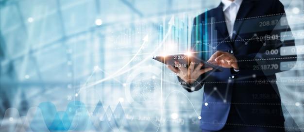 Uomo d'affari facendo uso della compressa che analizza i dati di vendite e il grafico del grafico di crescita economica. Foto Premium