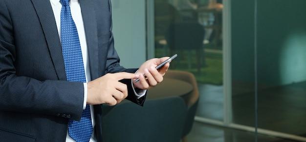 Uomo d'affari facendo uso dello smart phone all'interno del fondo dell'edificio per uffici Foto Premium