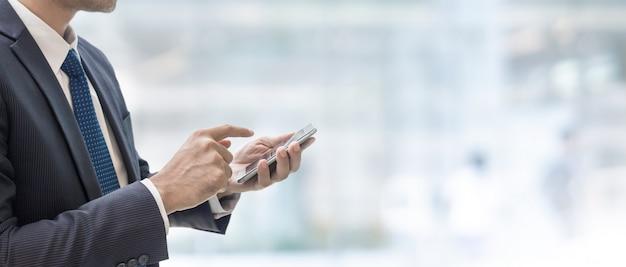 Uomo d'affari facendo uso dello smart phone nel fondo dell'insegna dello spazio interno del centro commerciale della sfuocatura Foto Premium