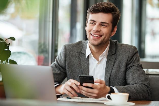 Uomo d'affari felice che si siede dalla tavola in caffè con il computer portatile e lo smartphone mentre distogliendo lo sguardo Foto Gratuite