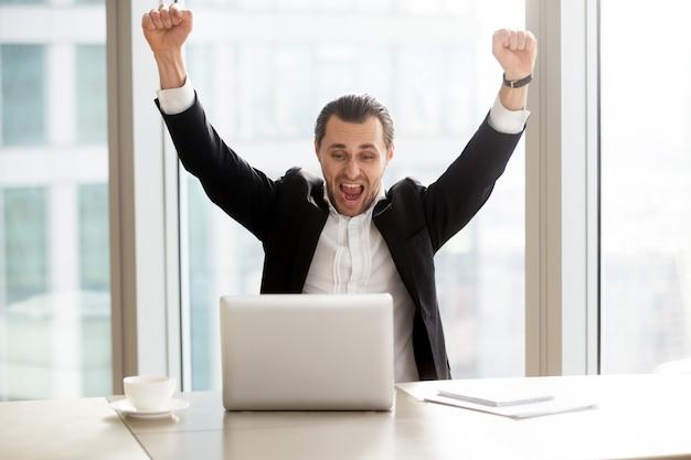 Uomo d'affari felice davanti al computer portatile Foto Gratuite