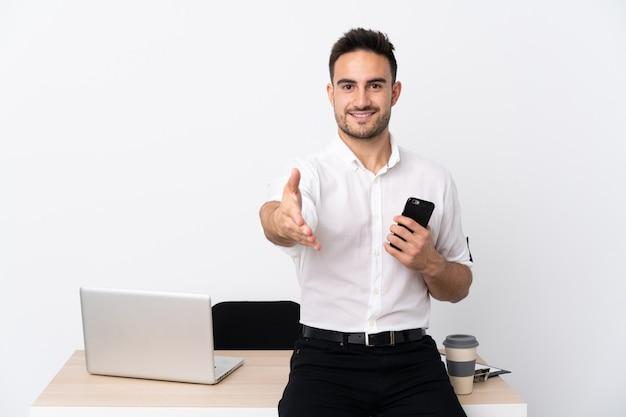 Uomo d'affari giovane con un telefono cellulare in un handshake sul posto di lavoro dopo un buon affare Foto Premium