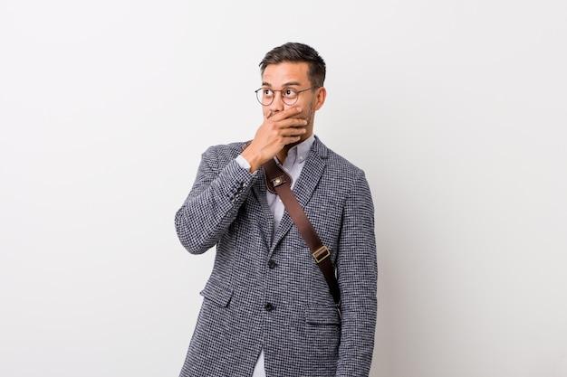 Uomo d'affari giovane contro un muro bianco pensieroso guardando e coprendo la bocca con la mano Foto Premium